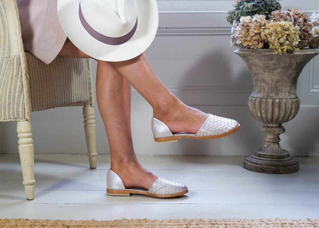 Woman wears flat Audrey shoe made from hand woven leather in pearl