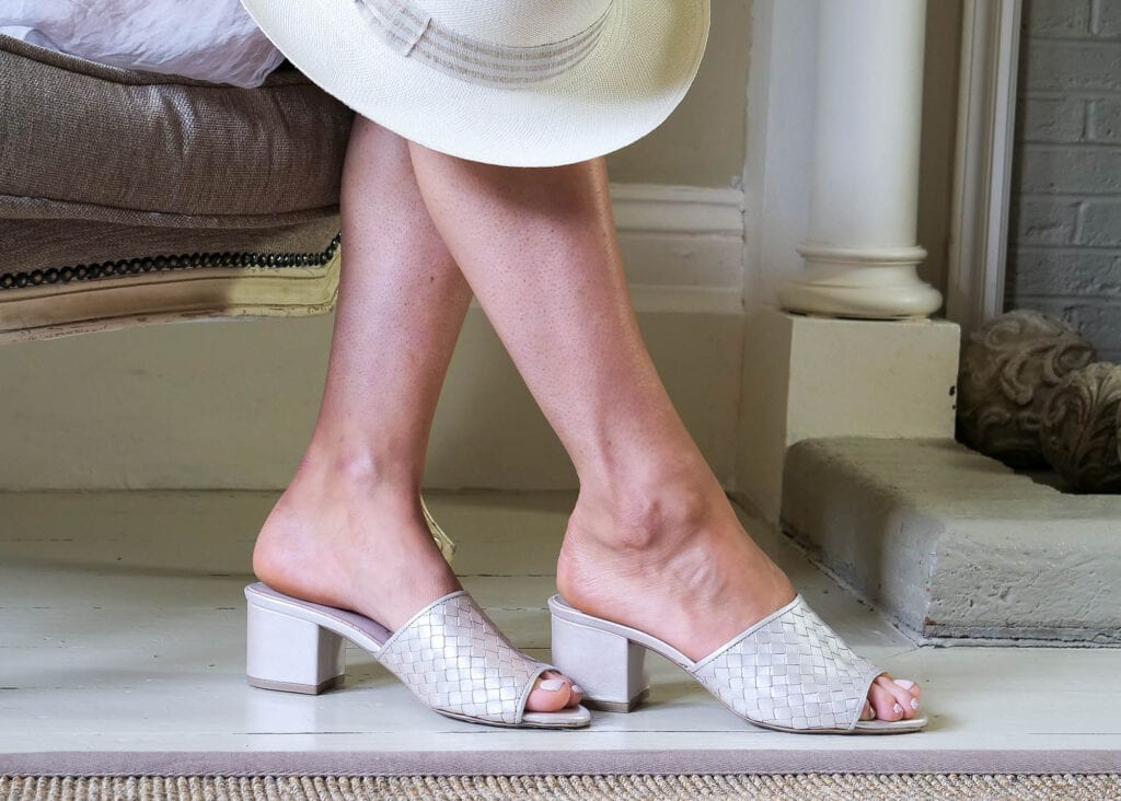 Lady wears a classic pair of mules in pearl coloured leather