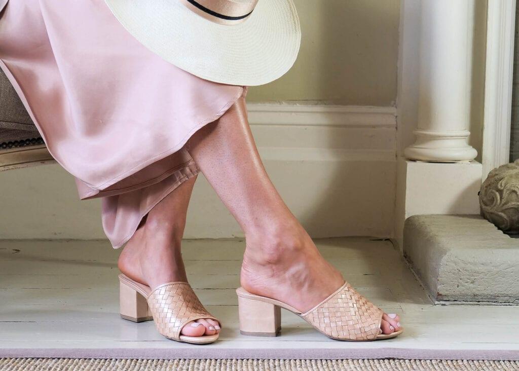 Lady wears woven leather, block heel mule