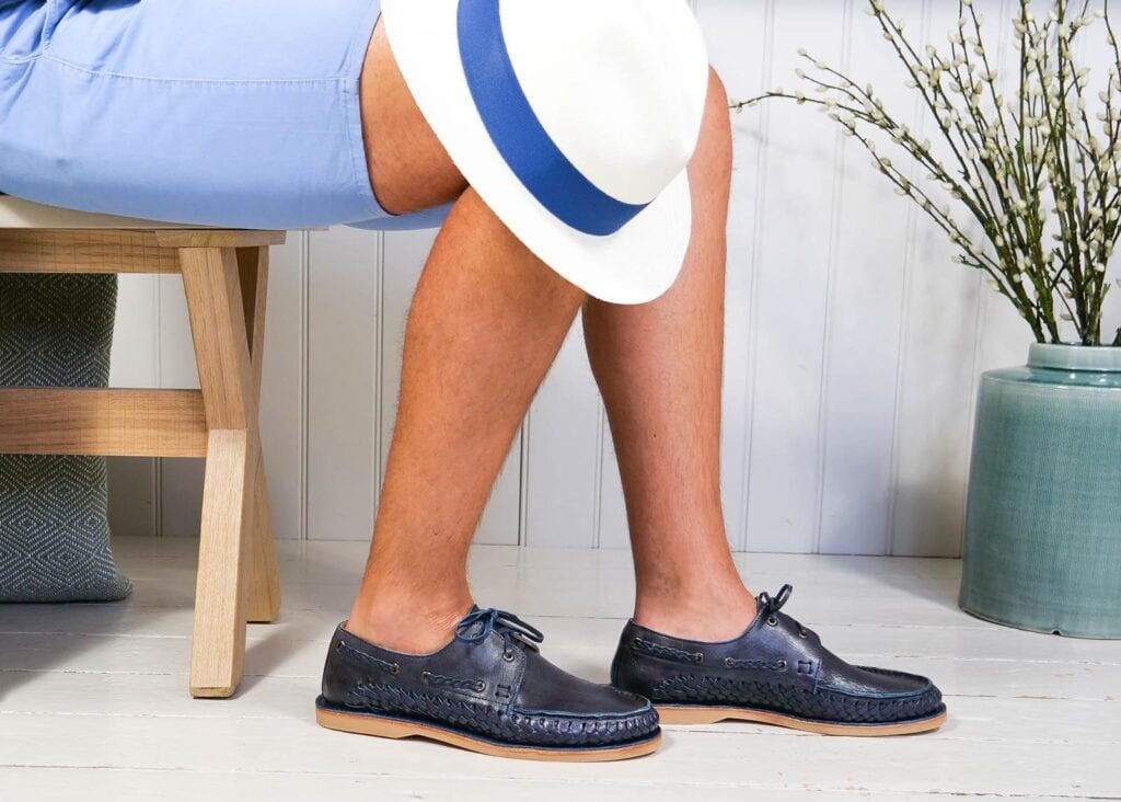 Man wears classic leather boat shoe in navy blue with rubber sole and leather laces