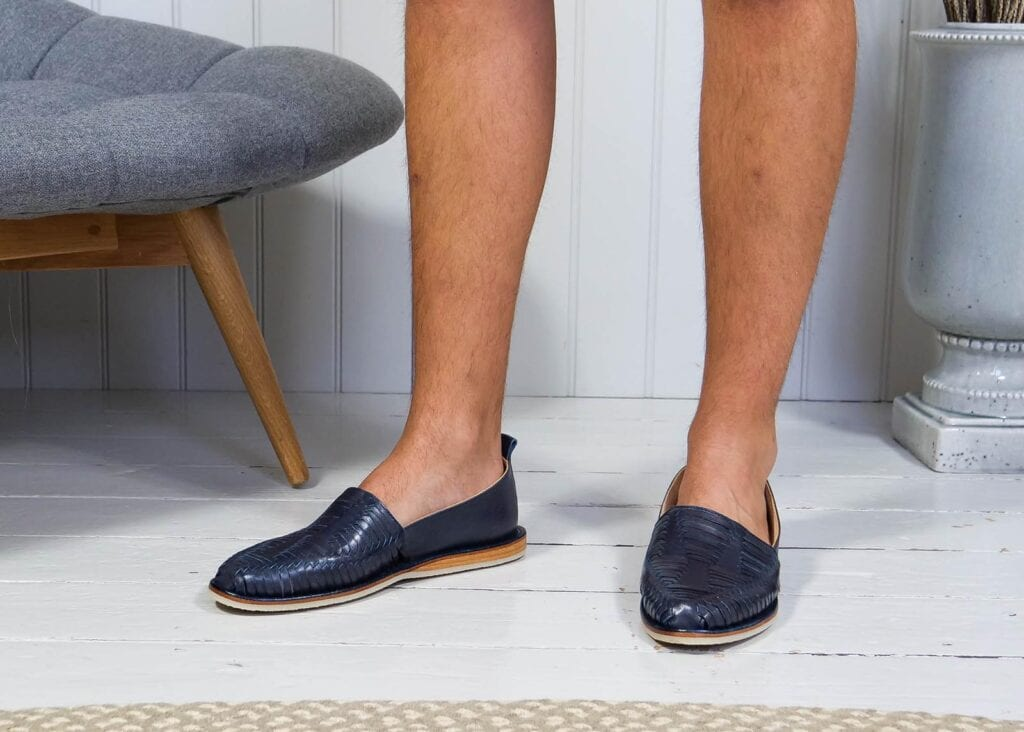 Man wearing slip on loafers with hand woven leather detail in navy blue