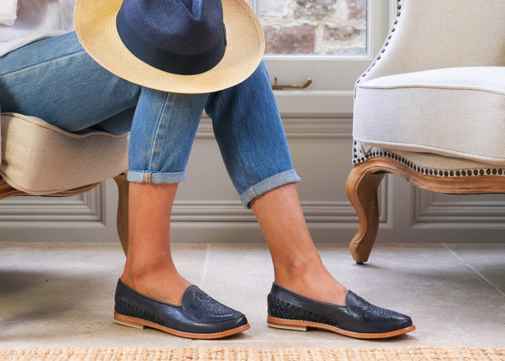 Woman wears classic slip on loafer made from sustainable navy blue leather