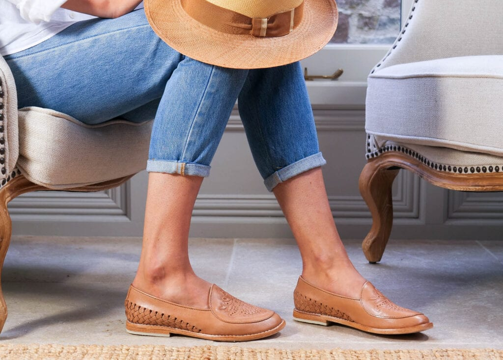 Women wears classic slip-on loafer in tan leather