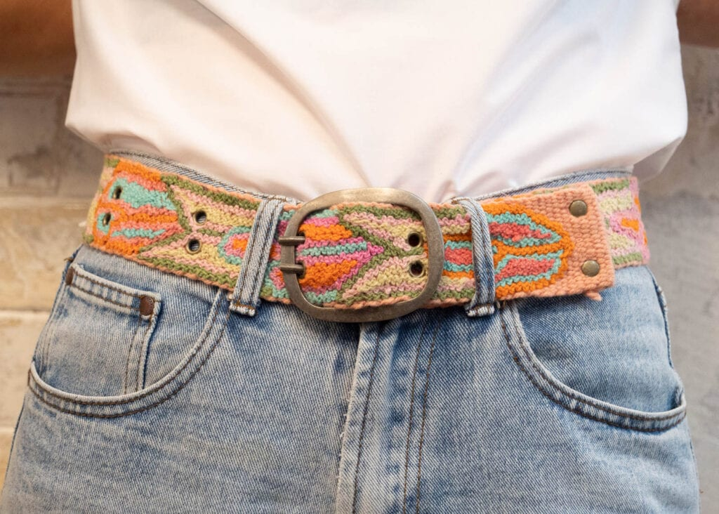 Close up of pink and turquoise hand-woven belt worn with blue jeans