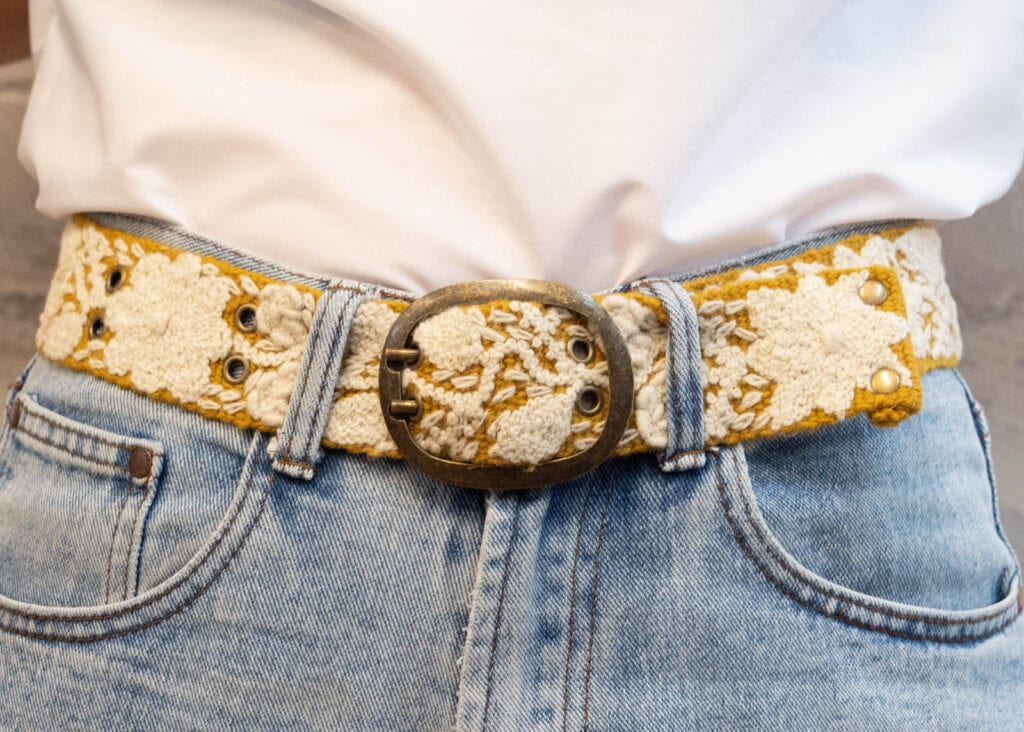 Women's close up of brass buckle with white woven wool
